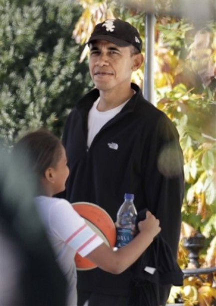 President Barack Obama waits as his daughter Sasha walks by after a basketball outing with both of his girls and some of their friends, Sunday, Nov. 28, 2010, in Washington. (AP Photo/J. Scott Applewhite)