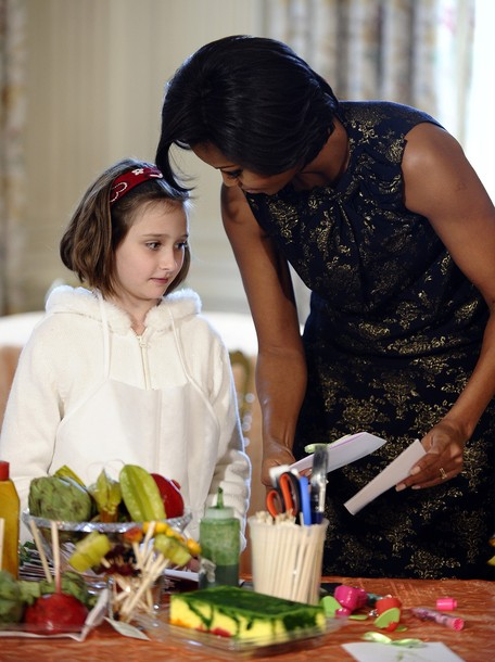 US First Lady Michelle Obama shows a holiday greeting card she made to a child in the State Dining Room to learn how to make holiday ornaments, cards and treats, at the White House in Washington, DC, on December 1, 2010. AFP PHOTO/Jewel Samad (Photo credit should read JEWEL SAMAD/AFP/Getty Images)