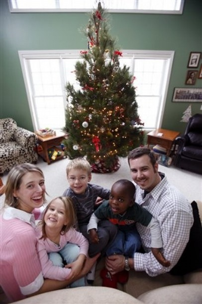 In this Friday, Dec. 17, 2010 picture, Brian and Emily Fletcher pose for a photo with their children, Cora, middle left, Isaac, center, and newly-adopted Sevil, middle right, at their home in Penfield, N.Y. Amid so much death and destruction in post-earthquake Haiti, an unprecedented commitment by the U.S. government allowed children in the adoption pipeline to be airlifted swiftly to America even though their paperwork was incomplete. In all, about 1,150 Haitian children have been placed with adoptive families across America. (AP Photo/David Duprey)