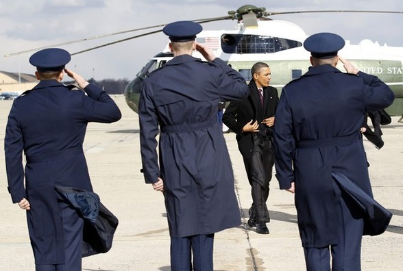 U.S. President Barack Obama pulls his coat closed as he boards Air Force One on a cold morning in Washington January 21, 2011. Obama is travelling to New York today to visit GE headquarters.    REUTERS/Kevin Lamarque (UNITED STATES - Tags: POLITICS)