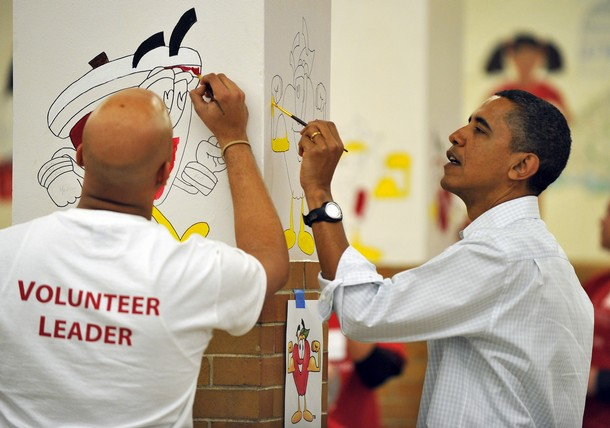 US President Barack Obama (R) paints on