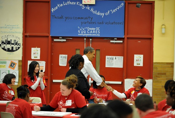 US President Barack Obama (C) greets other participants as he along with First Lady Michelle Obama as their daughters Malia and Sasha take part in a community service project at Stuart Hobson Middle School in celebration of the Martin Luther King, Jr. day of service in Washington, DC, on January 17, 2011. AFP PHOTO/Jewel Samad (Photo credit should read JEWEL SAMAD/AFP/Getty Images)