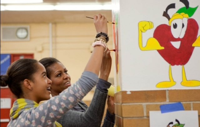 First Lady Michelle Obama and daughter Malia paint during a service project in the cafeteria of Stuart Hobson Middle School in Washington, D.C., Jan. 17, 2011. (Official White House Photo by Samantha Appleton)