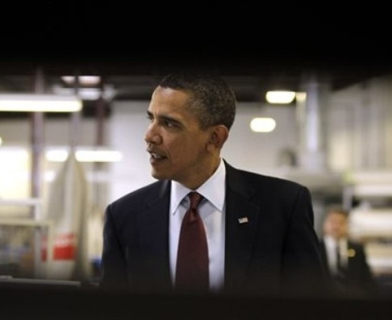 President Barack Obama is seen from behind pallets of vinyl window frames as he takes a tour of Thompson Creek Manufacturing, which makes custom replacement windows, Friday, Jan. 7, 2011, in Landover, Md. (AP Photo/Charles Dharapak)