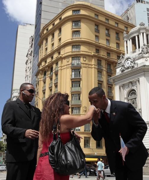 U.S. President Barack Obama impersonator, Rinaldo Americo, greets a tourist in Cinelandia Square in Rio de Janeiro